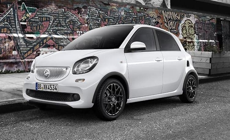 smart forfour hatchback parked next to a wall with graffiti