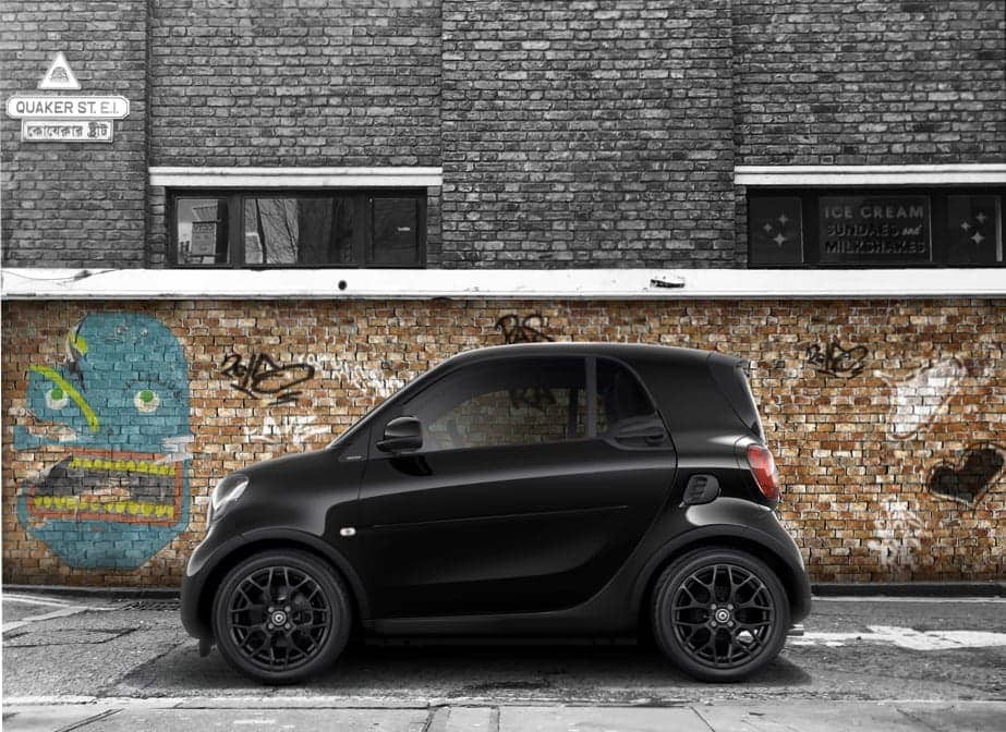 smart fortwo hatchback parked on a street with a graffiti wall backdrop.