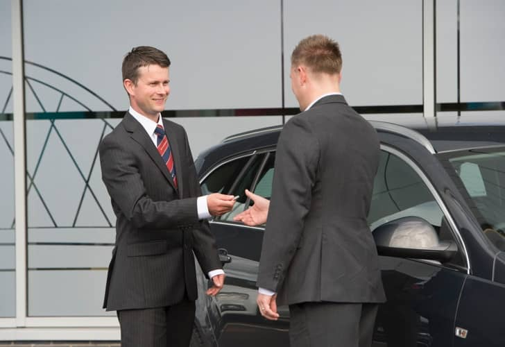 Man handing keys over to another guy while smiling.