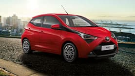 White Aygo and Yaris with city background.