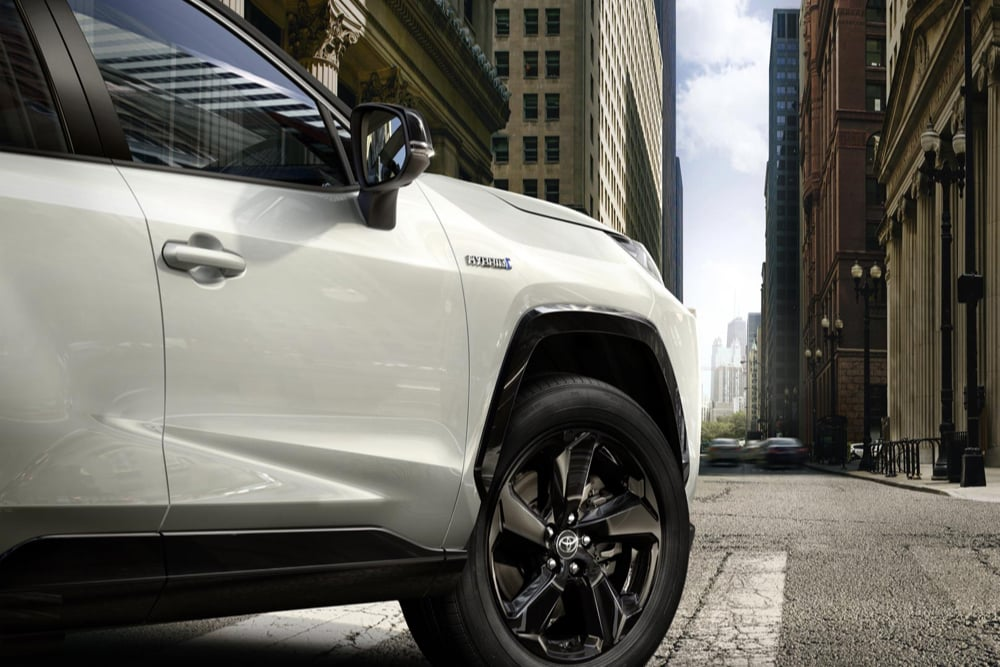 Close up of the front of a white Toyota RAV4 with black alloys.