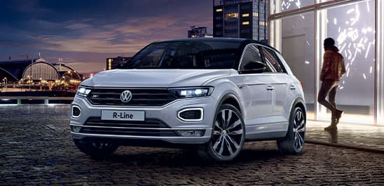 Blue Volkswagen T-Roc driving down a road.