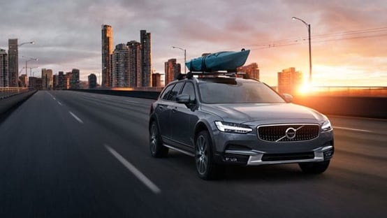 Volvo XC40 towing a speedboat along the coast.